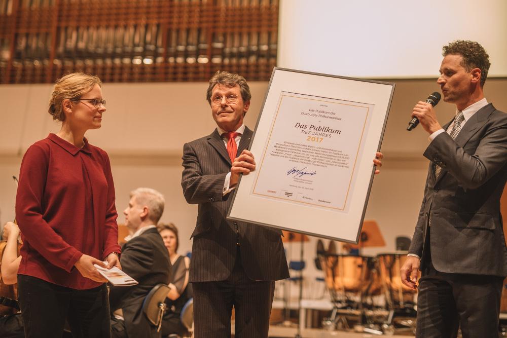 AlfredWendel (IntendantDuisburgerPhilharmoniker) nimmt die Urkunde entgegen, eingerahmt von Laurina Bleier (Konzertorganisation Duisburger Philharmoniker) und Gregor Burgenmeister (Herausgeber & Chefredakteurconcerti)
