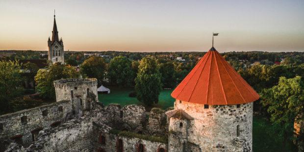 Cēsis: Die Deutschordensburg mit der St.-Johannis-Basilika im Hintergrund
