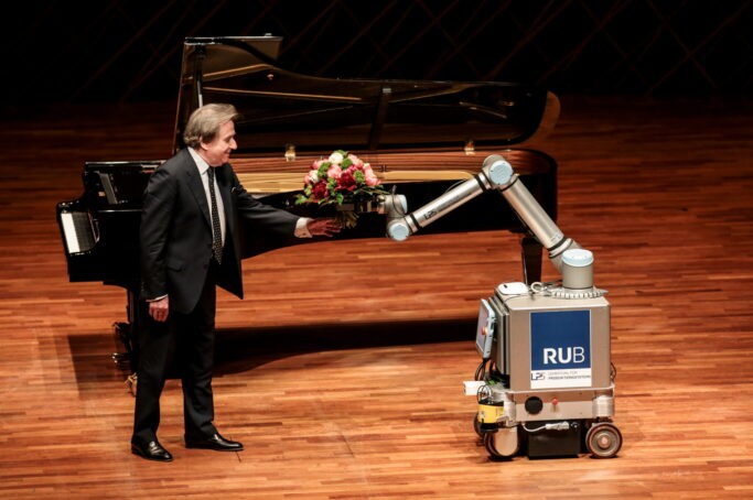 Rudolf Buchbinder empfängt Blumen von einem Roboter